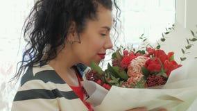 Mooie krullende vrouw met een schitterend boeket dichtbij het venster stock video
