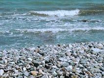 Mooie kust met golven en gekleurde stenen stock afbeeldingen