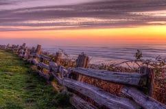 Mooie kustzonsondergang over een omheining Stock Afbeelding