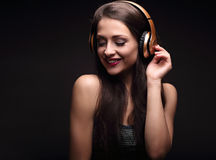 Mooie lachende lange haar jonge vrouw die de muziek in draadloze gele hoofdtelefoon op donkere zwarte achtergrond luisteren Royalty-vrije Stock Foto
