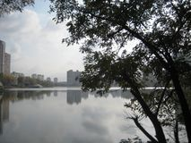 Mooie landschapsgang in de de herfstmiddag in het stadspark langs de oever van het meer stock foto