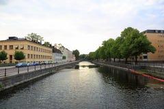 Mooie landschapsmening van rivieroever, Uppsala, Zweden, Europa Gele gebouwen en groene bomen op blauwe hemelachtergrond stock afbeeldingen