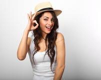 Mooie lange haar lachende vrouw die vingers o.k. teken i tonen Royalty-vrije Stock Foto's