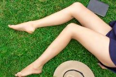 Mooie lange slanke sexy vrouwelijke benen die op het gras liggen Naast de hoed en het boek stock foto