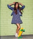Mooie langharige dame met een geel stuiverskateboard dichtbij a Royalty-vrije Stock Afbeeldingen