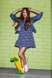Mooie langharige dame met een geel stuiverskateboard dichtbij a Stock Fotografie