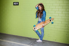 Mooie langharige dame met een houten lang skateboard dichtbij a Stock Foto