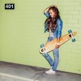 Mooie langharige dame met een houten lang skateboard dichtbij a Royalty-vrije Stock Fotografie