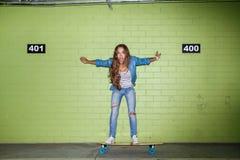 Mooie langharige dame met een houten skateboard dichtbij green Royalty-vrije Stock Afbeelding