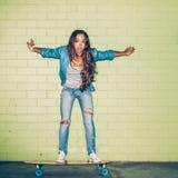Mooie langharige dame met een houten skateboard dichtbij green Royalty-vrije Stock Fotografie