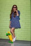 Mooie langharige vrouw met een geel stuiverskateboard dichtbij Royalty-vrije Stock Afbeeldingen
