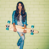 Mooie langharige vrouw met een houten lang skateboard dichtbij a Stock Foto