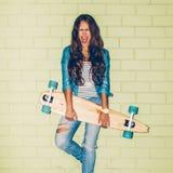 Mooie langharige vrouw met een houten lang skateboard dichtbij a Stock Afbeelding