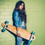 Mooie langharige vrouw met een houten longboard dichtbij green Royalty-vrije Stock Afbeelding
