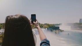 Mooie langzame motie achtermening die van gelukkige jonge toeristenvrouw wordt geschoten die foto's van ongelooflijk Niagara-wate stock video