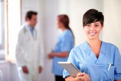 Mooie Latijnse verpleegster bij de blauwe eenvormige status Royalty-vrije Stock Foto's