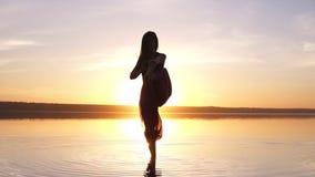 Mooie lengte op zonsondergangstrand, vrouw die yogaasana Utthita die Hasta Padagushthasana doen in het water blijven langzaam stock videobeelden
