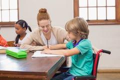 Mooie leraar die leerling in klaslokaal helpen Stock Afbeelding