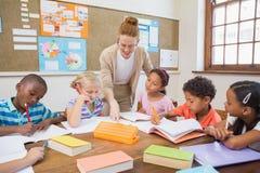 Mooie leraar die leerlingen in klaslokaal helpen Stock Afbeeldingen