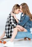 Mooie lesbische paarzitting en het koesteren op skateboard Stock Foto's