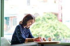 Mooie leuke Aziatische jonge onderneemster in de koffie stock afbeelding