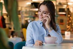 Mooie leuke Kaukasische jonge vrouw in de koffie, gebruikend mobiele telefoon en drinkend koffie het glimlachen royalty-vrije stock afbeelding