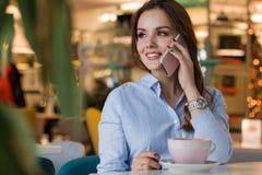 Mooie leuke Kaukasische jonge vrouw in de koffie, gebruikend mobiele telefoon en drinkend koffie het glimlachen stock foto
