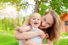 Mooie leuke moeder met weinig babyjongen die pret hebben in openlucht Portret van mamma met pretkind het glimlachen in de groene  royalty-vrije stock fotografie