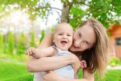 Mooie leuke moeder met weinig babyjongen die pret hebben in openlucht Portret van mamma met pretkind het glimlachen in de groene  stock afbeeldingen