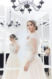 Mooie leuke tedere jonge meisjesbruid in huwelijkskleding in spiegels met avondhaar en zachte lichte samenstelling Stock Afbeeldingen