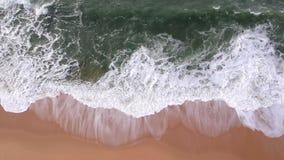 Mooie luchtdiehommel van oceaangolven wordt geschoten die op gouden zandig strand in Portugal tijdens de zomer breken stock footage