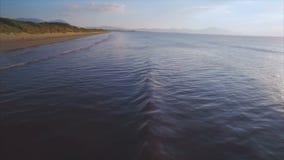 Mooie luchtlengte van overzeese golven die strand bereiken, stock videobeelden
