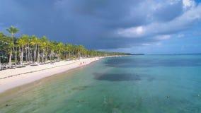 Mooie luchtvlucht over het tropische strand van het paradijseiland met lopende toeristen en palmen en hotels, toevluchtgebied stock video