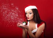 Mooie make-up gelukkige vrouw in het kostuum die van de Kerstman op s blazen stock afbeeldingen