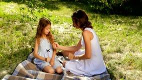 Mooie mamma en dochter die een spel van rots, document, schaar in het park spelen stock videobeelden