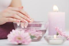 Mooie manicure met orchidee, kaars en handdoek op witte wo Stock Afbeeldingen