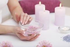 Mooie manicure met orchidee, kaars en handdoek op witte wo Royalty-vrije Stock Foto's