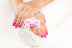 Mooie manicure met roze orchidee en handdoek stock foto