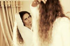 Mooie maniervrouw die met lange krullende haren in de spiegel kijken Stock Foto