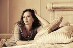 Mooie maniervrouw met lange krullende haren in een slaapkamer Royalty-vrije Stock Fotografie