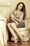 Mooie maniervrouw met lange krullende haren in een slaapkamer Royalty-vrije Stock Afbeelding