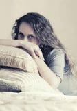 Mooie maniervrouw met lange krullende haren in een slaapkamer Stock Foto