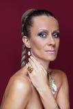 Mooie maniervrouw met make-up en gouden juwelen Stock Foto's