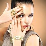 Mooie maniervrouw met zwarte make-up en gouden manicure Stock Foto's