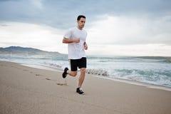 Mooie mannelijke atletenlooppas langs het strand langs het overzees, de achtergrond van het bergstrand Stock Foto