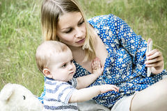 Mooie mather en een zitting van de babyjongen op gras en het bekijken elektronisch apparaat royalty-vrije stock afbeelding