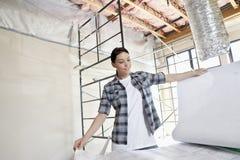 Mooie medio volwassen contractant die de bouw van plannen bij bouwwerf bekijken stock foto's