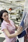 Mooie medio volwassen vrouw die plastiek zetten aan droge schoongemaakte kleren in laundrette Royalty-vrije Stock Fotografie