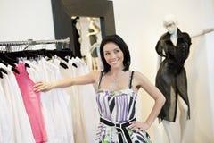 Mooie medio volwassen vrouw die zich door klerenrek bevinden in manierboutique stock fotografie