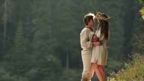 Mooie meermin in bloemkroon en jonge mens in liefde Magisch paar die op achtergrond van oude groene geheimzinnigheid omhelzen stock videobeelden